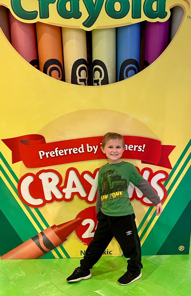 happy boy in front of crayon box at plano crayola experience